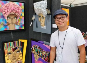 Artist posing with his work at Tallahassee's chain of parks festival